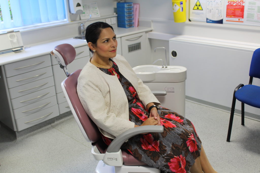 Priti Patel MP tries out a dentist chair