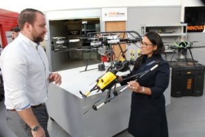 Priti Patel holds a drone, while the technology is explained to her by James Arnett, Texo DSI's Head of Operations & Remote Sensing