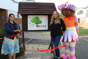 Priti Patel MP cutting the ribbon to declare Pickles Playhouse open, with help from new owner Marie Downes and a friend!