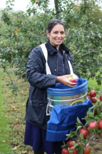 Priti Patel with fruit picker's basket, helps to gather in the harvest.