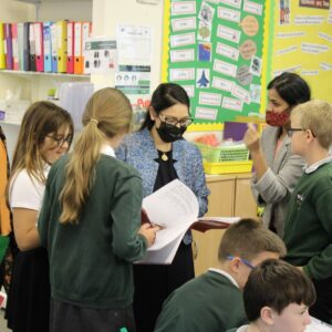 Pupils at Powers Hall Academy queue up to show off their handwriting skills to Priti Patel.