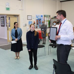 Head Teacher, Mike Wood presents Katie Mason with a special certificate of achievement.