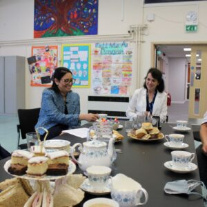 Priti takes cream tea with Katie Mason (left), Susannah Edom-Baker - CEO of Attain Partnership Trust which runs the School (far end of table) and Tina Townsend of Acacia Business Services Ltd
