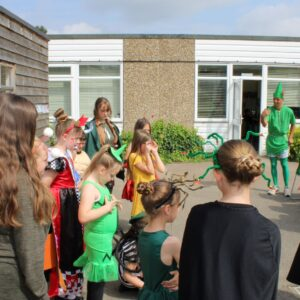 Pupils at Powers Hall Academy show off their Get Witham Reading costumes to Priti Patel, while Peter Pan looks on.