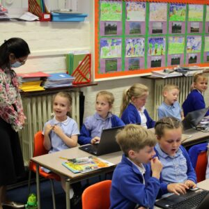 A pupil at Rivenhall C of E Primary School discusses her reading project with Witham MP, Priti Patel